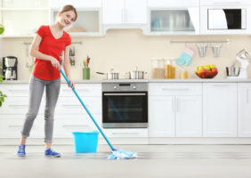 A woman cleans the kitchen floor with a mop